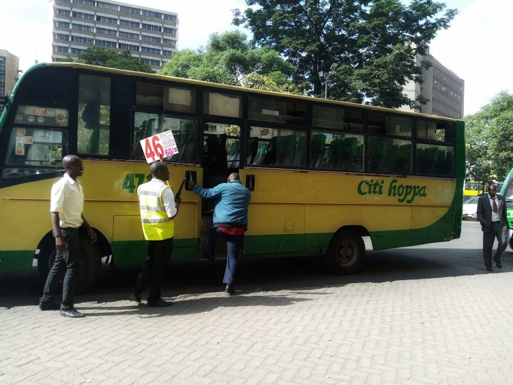 Photo of A man boarding a matatu