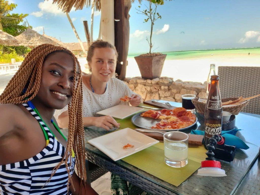 Two women having pizza near the beach by weonboard.com