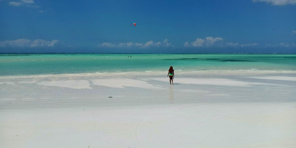 A woman standing at the beach in zanzibar by weonboard.com